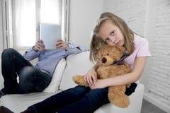 互联网使用数字式片剂垫的上瘾者父亲忽略小哀伤的女儿使拥抱玩具熊不耐烦 库存照片