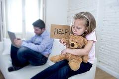 互联网使用数字式片剂垫的上瘾者父亲忽略小哀伤的女儿使拥抱玩具熊不耐烦 免版税库存图片