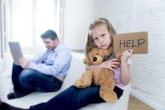 互联网使用数字式片剂垫的上瘾者父亲忽略小哀伤的女儿使拥抱玩具熊不耐烦 免版税图库摄影