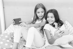 互联网冲浪和缺席父母亲情况通知 智能手机上网 女孩姐妹穿睡衣繁忙与 免版税库存图片