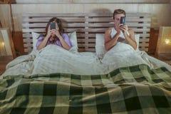 互联网在忽略的床上的上瘾者夫妇使用在线约会的社会媒介app在挥动的手机和在relationsh 免版税图库摄影
