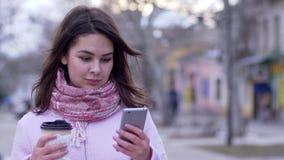 互联网技术,有电话的可爱的妇女在胳膊喝茶和去在镇特写镜头 股票录像