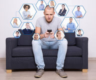 互联网概念-英俊的人坐沙发和使用聪明 免版税库存图片