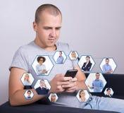互联网瘾概念-英俊的人坐沙发和我们 免版税库存照片