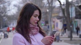 互联网瘾,有智能手机的微笑的女孩在手上走在露天特写镜头的 影视素材