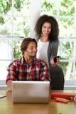 从互联网的现代夫妇购买有巧妙的电话和膝上型计算机的 库存图片