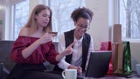 互联网购物,微笑的不同种族的朋友女孩为薪水网上购买使用塑料卡片和手提电脑 股票录像
