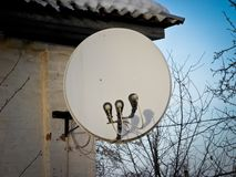互联网通信和在房子的屋顶安装的电视卫星盘在绿色树背景 免版税图库摄影