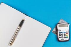 互联网银行业务、付款卡片和开放纸笔记本的电子密码发电器有在蓝色背景的笔的 免版税图库摄影