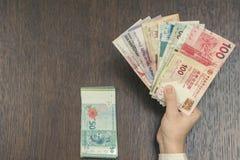 五东南亚货币钞票在女性手和分开的捆绑上令吉 开户和旅行概念 库存图片