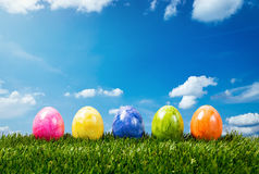 五个五颜六色的复活节彩蛋行在绿草的 免版税库存照片