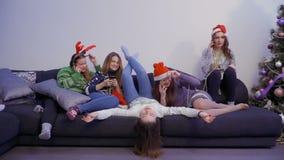 五个女孩使用放松他们的电话在沙发 股票视频