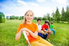 五个愉快的孩子坐在行的椅子户外 免版税库存图片