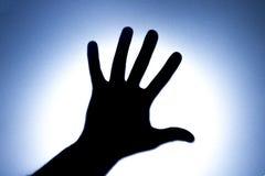 五个手指剪影在一只人` s手上的有一个明亮的亮点的 恳求的概念帮助或问候的 蓝色 免版税图库摄影
