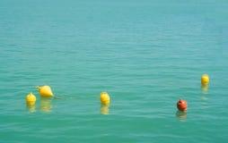 五个明亮的黄色和橙色标志漂浮漂浮在蓝色turq 免版税库存图片