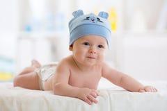 五个月男婴在躺下在毯子的滑稽的帽子weared 免版税库存照片