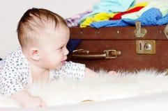 五个月婴孩看一个老手提箱 库存图片