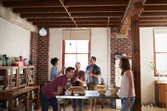 五个朋友在厨房里站立谈话在咖啡 免版税库存照片