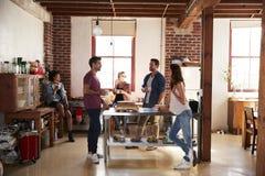 五个朋友谈话在咖啡在厨房里,全长 免版税库存照片