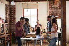 五个朋友食用咖啡在厨房,四分之三长度 库存图片