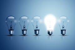 五个电灯泡和他们中的一个发光 免版税库存照片