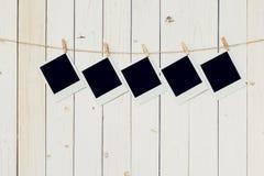 五个5blank垂悬在白色木背景的照片框架与 图库摄影