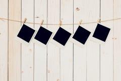 五个5blank垂悬在白色木背景的照片框架 库存图片