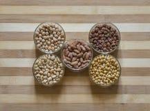 五分类了在碗的未加工的豆类,安置在一块砧板 免版税库存图片
