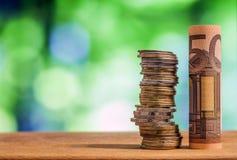 五十欧元在绿色blurre滚动了票据钞票,与欧洲硬币 库存图片