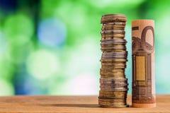 五十欧元在绿色blurre滚动了票据钞票,与欧洲硬币 免版税库存图片