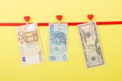 五十美元、兹罗提和欧元在晒衣夹,黄色背景垂悬 库存图片