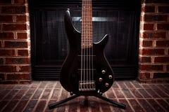 五在壁炉前面的串低音吉他 库存照片