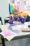 五岁做图画的女孩在水 与油漆的Ebru艺术由水表面 图库摄影