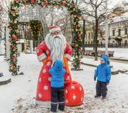 五岁的孪生,在圣诞节装饰的街道上 库存图片