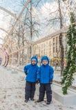 五岁的孪生,在圣诞节装饰的街道上 库存照片