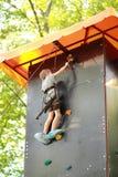 五岁的男孩到达了上升的岩石墙壁的上面外面在夏天公园和敲响赢取的响铃 免版税库存照片