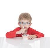 五岁的男孩坐在一张白色桌上并且吃酸奶 库存照片