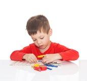 五岁的男孩坐在一张白色桌上并且扮演一位电子设计师 免版税图库摄影