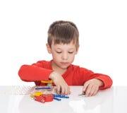 五岁的男孩坐在一张白色桌上并且扮演一位电子设计师 免版税库存图片