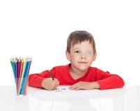 五岁的男孩坐在一张白色桌上并且画铅笔,左眼睛困住与膏药 库存图片