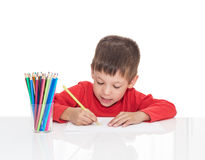 五岁的男孩坐在一张白色桌上并且画铅笔 库存图片