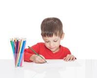 五岁的男孩坐在一张白色桌上并且画铅笔 库存照片