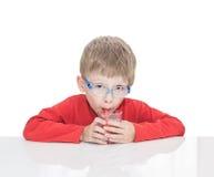 五岁的男孩坐在一张白色桌上 免版税图库摄影