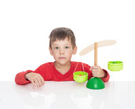 五岁的男孩坐在一张白色桌和戏剧上与木标度 库存图片
