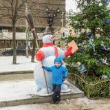 五岁的男孩,在圣诞节装饰的街道上 图库摄影