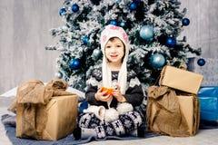 五年的小女孩孩子坐地板在用玩具装饰的圣诞树附近,球 在手上拿着一个桔子 免版税图库摄影