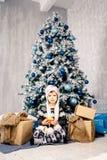 五年的小女孩孩子坐地板在用玩具装饰的圣诞树附近,球 在手上拿着一个桔子 库存照片