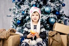 五年的小女孩孩子坐地板在用玩具装饰的圣诞树附近,球 在手上拿着一个桔子 库存图片