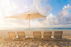 五张海滩睡椅和伞在白色沙子靠岸与多云蓝天和太阳 免版税图库摄影