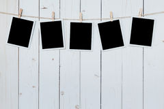 五张照片框架空白垂悬在木板背景 库存照片
